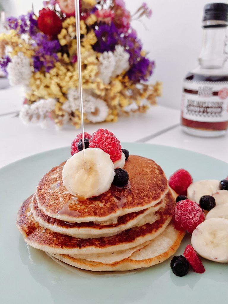 Pancakes à la banane avec du sirop d'érable et des fruits rouges