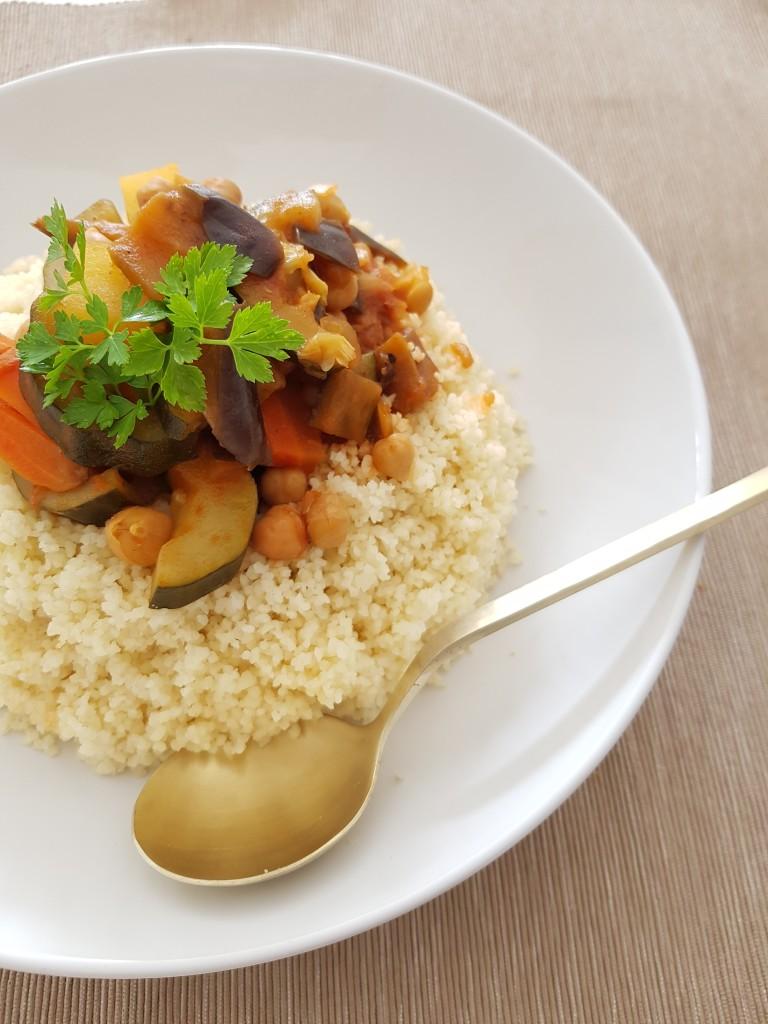 De la semoule de blé, couronnée par un couscous aux légumes d'été (aubergine, courgette, tomates), carottes, pois chiches, raisins secs, coriandre