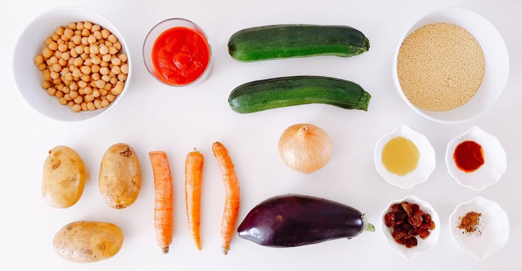 Les ingrédients exposés sur un fond blanc : semoule de blé, aubergine, courgette, pomme de terres, oignons, tomates, carottes, pois chiches, raisins secs, épices