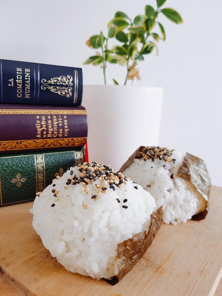 Une boule de riz collant à sushi, entouré d'alge nori. Des livres empilés en arrière plan
