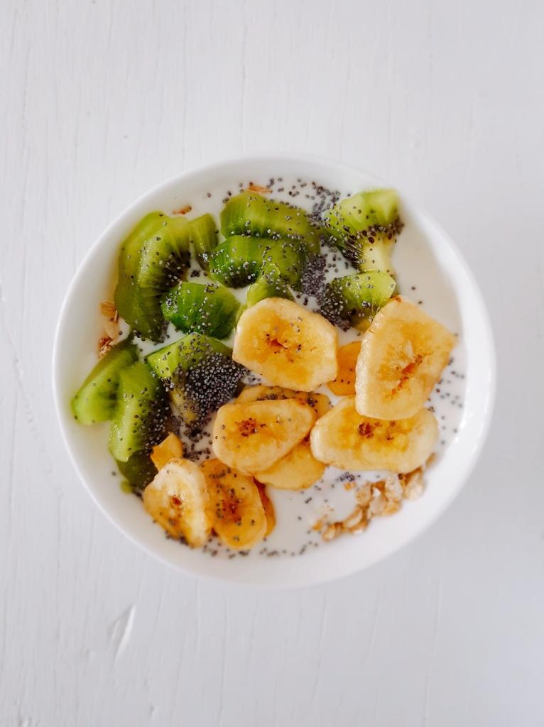 Un bol blanc avec yaourt et flocons d'avoine, en toping des bananes séchées et des kiwi